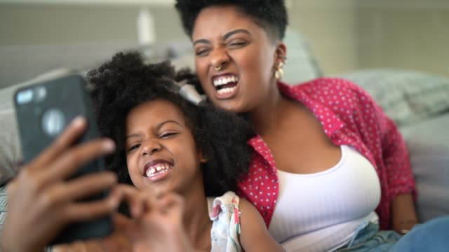 sisters taking a selfie sitting in the couch - video call with family video stock e b–roll