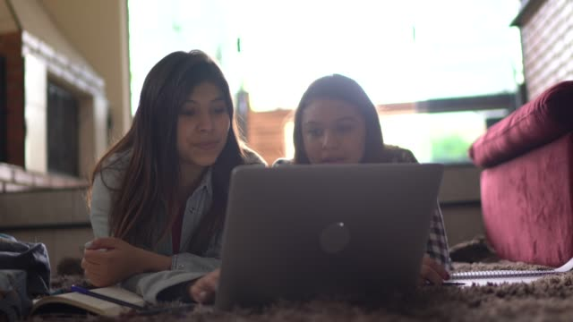 sisters talking on a laptop on online classes at home - didattica a distanza video stock e b–roll