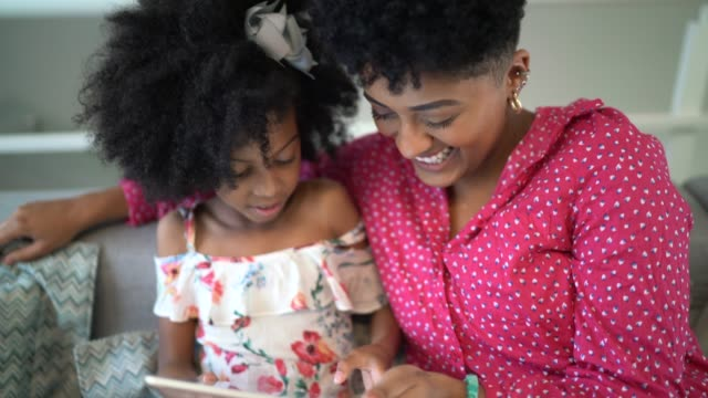 Sisters using a digital tablet at home