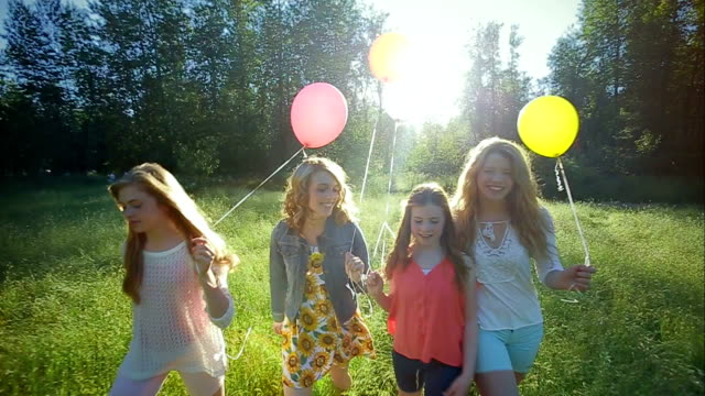 Sisters Walk Together (Toward Camera) In A Sunny Field, With Colorful Balloons video