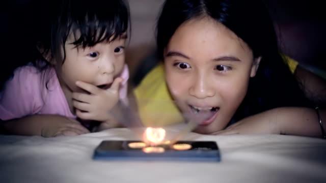 vídeos de stock, filmes e b-roll de irmãs assista a halogram em smartphone - holograma