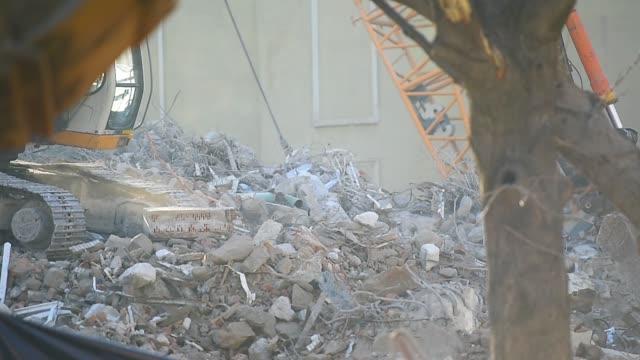 破片を運ぶ掘削機と取り壊された建物のサイト - 残骸点の映像素材/bロール