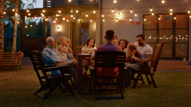 sitting at the dinner table handsome young man plays the guitar for a friends. family and friends listening to music at the summer evening garden party celebration. - family home video stock e b–roll
