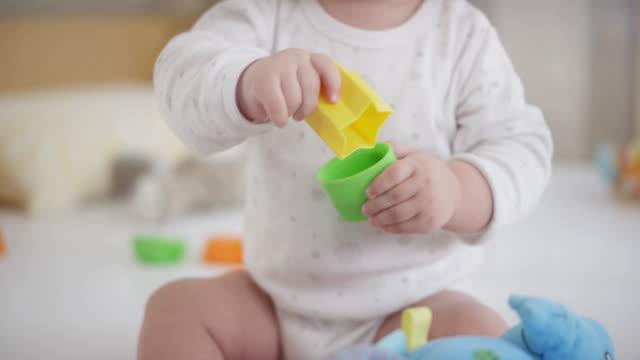 stockvideo's en b-roll-footage met vergadering jongetje spelen met kunststof vorm blokken - baby toy