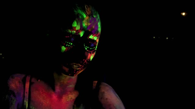 Sitting beautiful sexy girl with ultraviolet paint on her face and body. Girl with color neon bodyart video