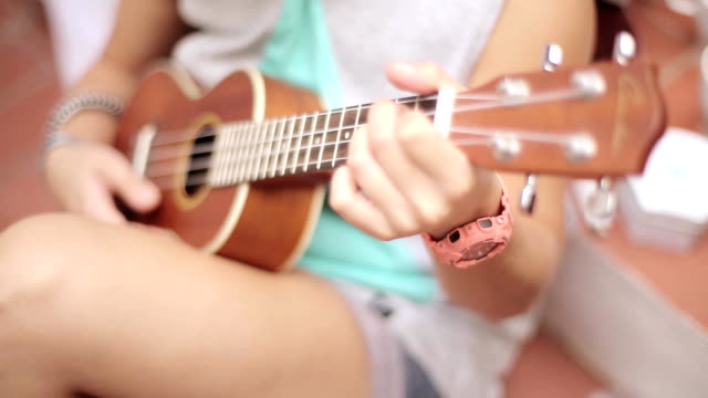 Sitting girl in shorts playing ukulele guitar on street. Summer sunny day. Music. Strings. Sound video