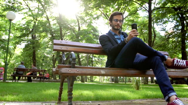 sitting in park and texting - садовая скамья стоковые видео и кадры b-roll