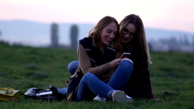 Sitting on a grass and looking at mobile phone video