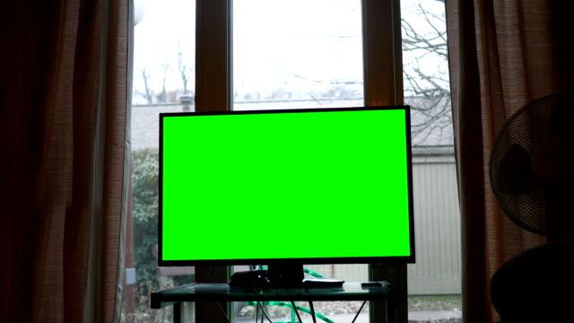 hd テレビは、角ピンに緑色の画面で地上階のアパートの窓の前にスタンドに座って - 居間点の映像素材/bロール