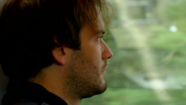 sitting on the train and travelling: young pensive man looking out the window video