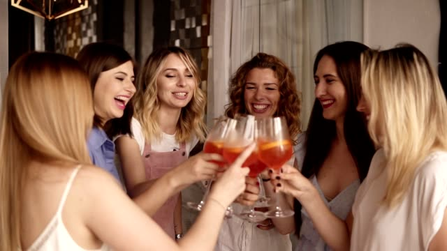 six beautiful stylish women in elegant casual outfit celebrating and drinking alcohol cocktails. cheers. beautiful, modern interior. hen party. slow motion - bachelorette party stock videos and b-roll footage
