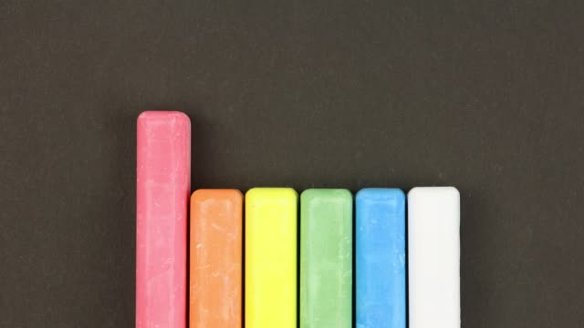 six colored children crayons on black background lined in row, come out sequentially, close-up, loop video, stopmotion animation, kindergarten education concept