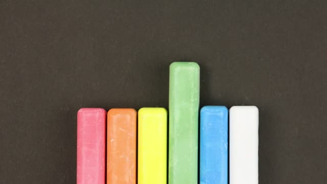six colored children crayons on black background lined in row, first crayons come out sequentially then randomly, close-up, loop video, stopmotion animation, kindergarten education concept