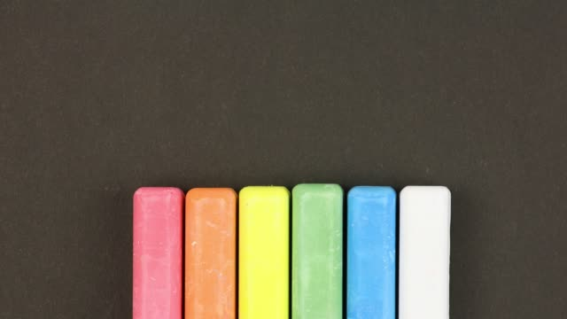 six colored children crayons on black background lined in row, rises sequentially, close-up, loop video, stopmotion animation, kindergarten education concept