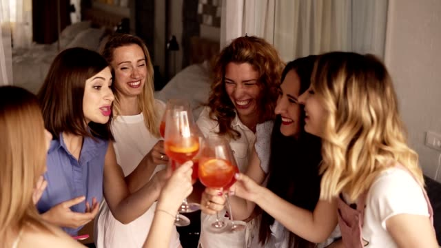six girls standing in a close circle and communicating. celebrating, drinking beverages from glasses. cheers. indoors. bright, fancy interior. high angle footage - bachelorette party stock videos and b-roll footage