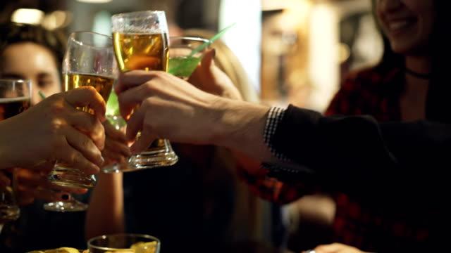 Six mains tintements de verres avec bières et cocktails au café douillet. Visages heureux de beaux jeunes gens l'alcool en arrière-plan. Concept de vacances célébration jeunesse. - Vidéo