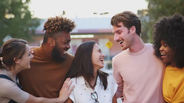 Six millennial hipster friends standing in a city street smiling to camera, panning shot