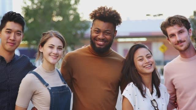 stockvideo's en b-roll-footage met zes duizendjarige hipster vrienden staan in een stad straat glimlachen naar de camera, panning shot - street style