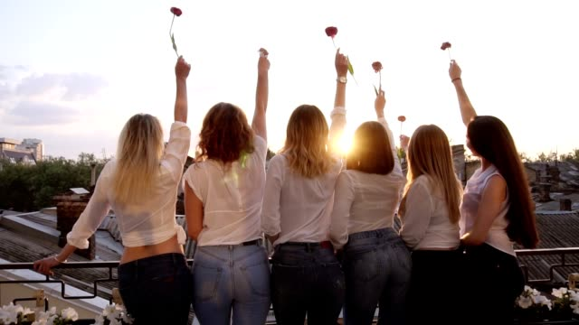 six seductive young women are standing on a terrace in a row from their back. wearing casual clothes, white shirts and jeans. raising up their hands with a flower. front view - kobiecość filmów i materiałów b-roll