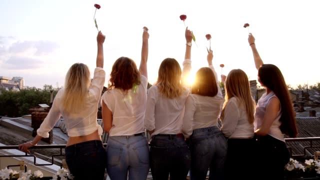 stockvideo's en b-roll-footage met zes verleidelijke jonge vrouwen staan op een terras in een rij van hun rug. het dragen van casual kleding, witte shirts en jeans. het verhogen van hun handen met een bloem. vooraanzicht - vrouwelijkheid