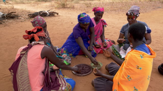 Six woman and a baby sitting on the ground and eating sorghum porridge, Zimbabwe