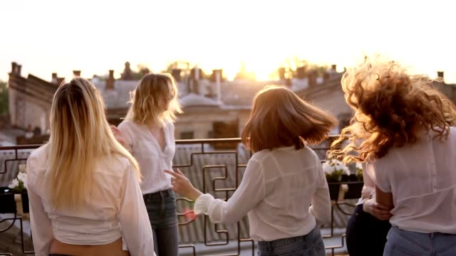 six women are hanging out together on the terrace. all in the same style clothes. dancing and jumping. casual clothes. cityscape background. hen party concept. dusk. slow motion - bachelorette party stock videos and b-roll footage
