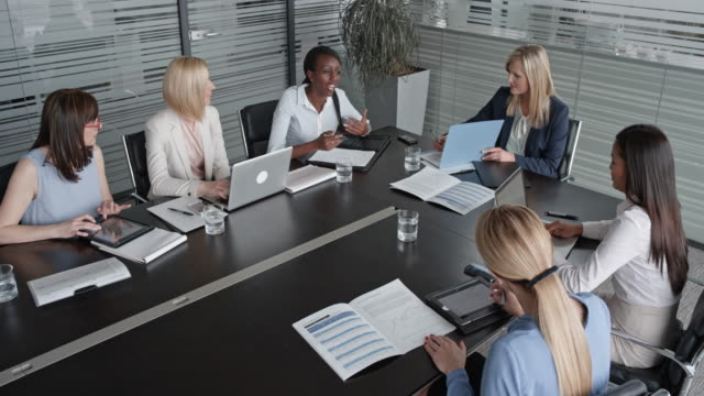 CS Six women of different ethnicity in a project meeting in the conference room