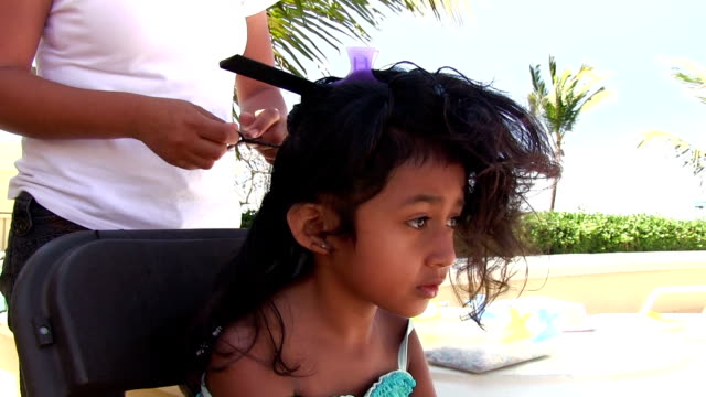 Six year old Mexican girl getting her hair braided video