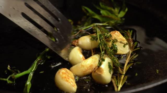 sizzling garlic, rosemary and tarragon roasting in olive oil - чеснок стоковые видео и кадры b-roll