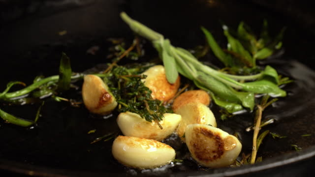 sizzling garlic, rosemary and tarragon roasting in olive oil - olio d'oliva video stock e b–roll