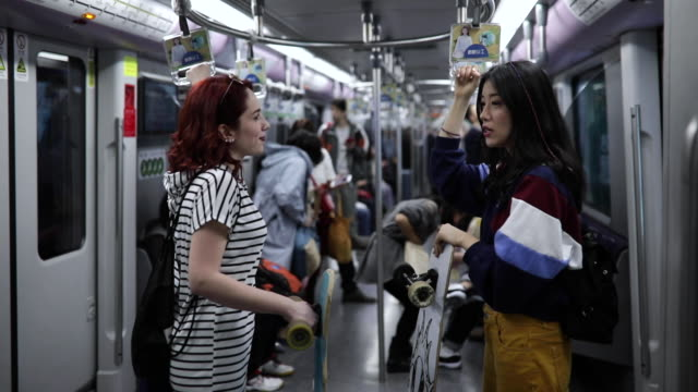 Skateboard girl in subway train Caucasian woman and her Chinese friends riding in the subway train, with long boards, talking and standing red lipstick stock videos & royalty-free footage