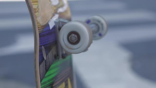 skateboard hjul spinning i närbild skott, grönt, gult och blått ombord hålls av en skater pojke, tilt upp slow motion 4k. street i suddig bakgrund. - wheel black background bildbanksvideor och videomaterial från bakom kulisserna
