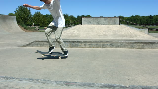 Skateboarder does flip trick, slow motion video