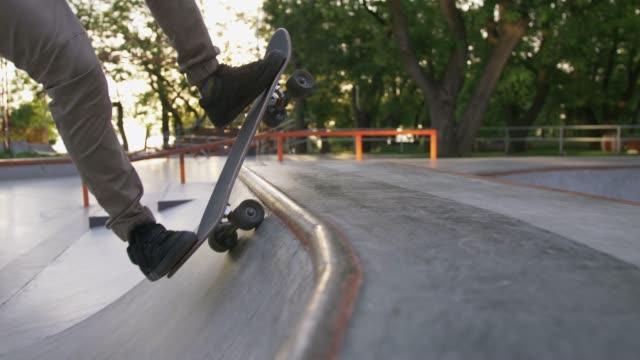 skateboardåkare gör ett trick i en betong skateboardpark, närbild, långsam rörelse - skatepark bildbanksvideor och videomaterial från bakom kulisserna