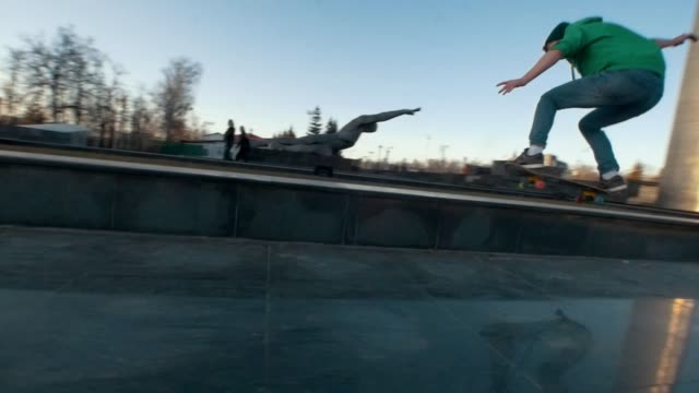 skateboarder failed tricks on the ramp outdoors in sunset - skateboard stock videos & royalty-free footage