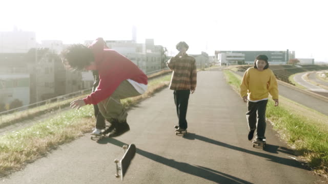 スケートボードのトリック(スローモーション)を実行する友人を撮影するスケートボーダー - 日本人のみ点の映像素材/bロール