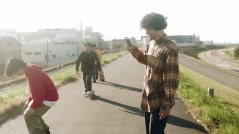 vídeos y material grabado en eventos de stock de skateboarder filmando amigos realizando trucos de skateboarding (movimiento lento) - actividades recreativas