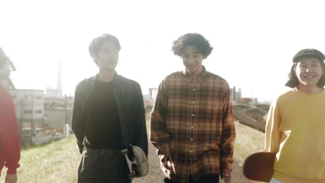 stockvideo's en b-roll-footage met skateboarder vrienden lopen en praten (slow motion) - oost azië