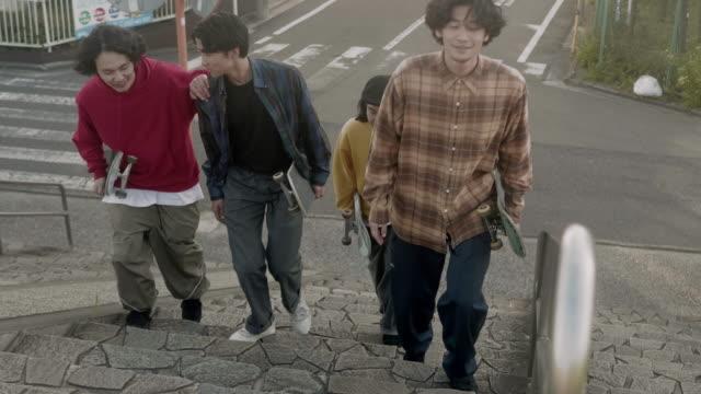 skateboarder friends walking and talking (slow motion) - cultura della gioventù video stock e b–roll