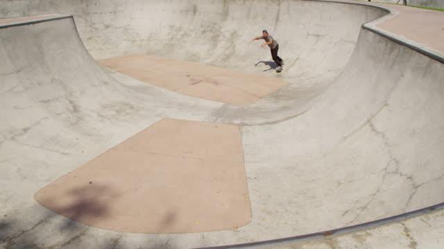 Skateboarder grinds bowl at skatepark video