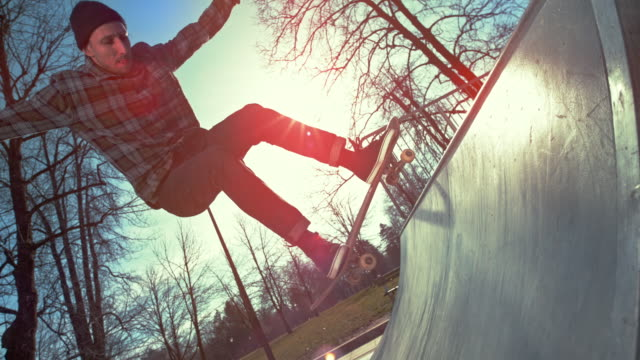 vidéos et rushes de slo mo skateboarder sauter avec sa planche à roulettes et la poussière rouge et bleue est dispersé dans l'air - 30 34 ans