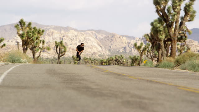 Skateboarder rides on road in desert