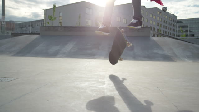 SLOW MOTION: Skateboarder riding and jumping in a skatepark