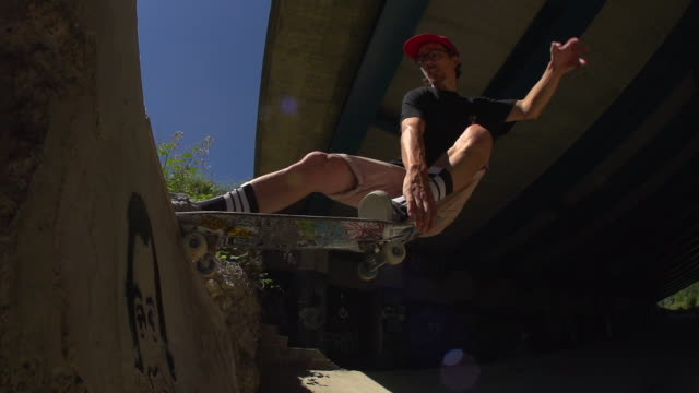 A Skateboarder riding in an urban environment under a bridge. video