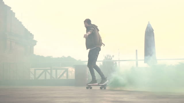 Skateboarder riding outdoors at sunset. Handsome guy riding on a skateboard with green smoke. Outdoors