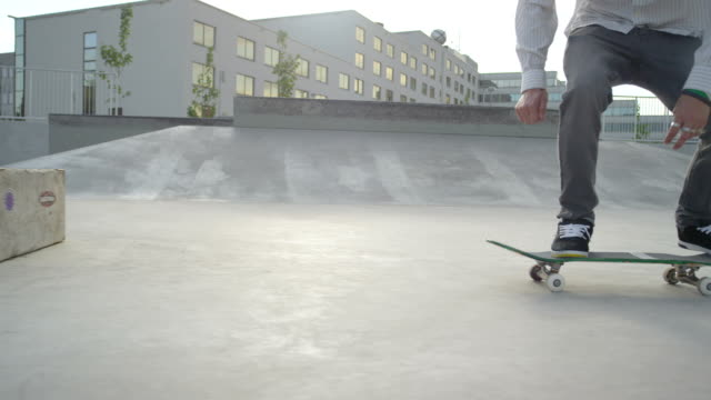 SLOW MOTION CLOSE UP: Skateboarder riding the ramp in skatepark video