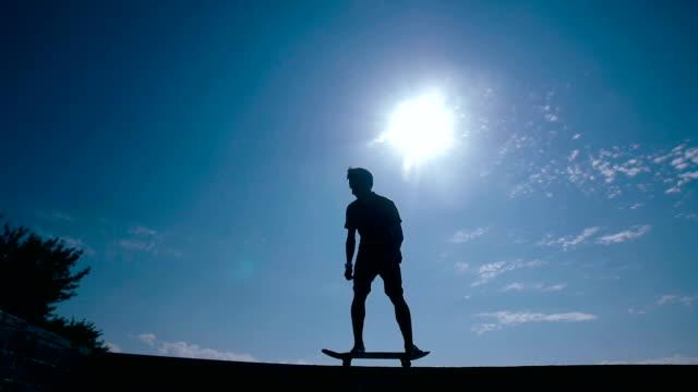 Skateboarder silhouette skateboarding on a sky background at sunset. Slow motion video