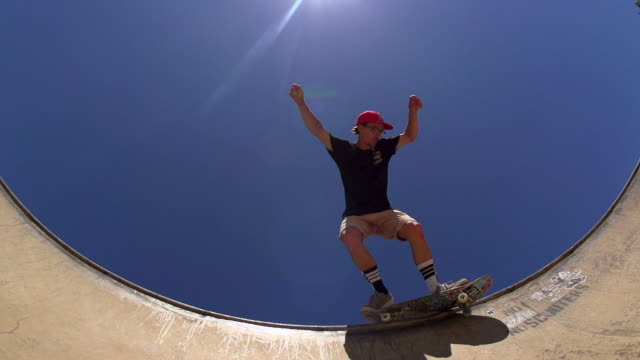 A Skateboarder Sliding the lip of a skateboard park bowl. video