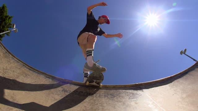 a skateboarder sliding the lip of a skateboard park bowl. - skateboard stock videos & royalty-free footage