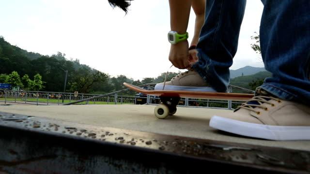 skateboarder tying shoelace at skatepark video